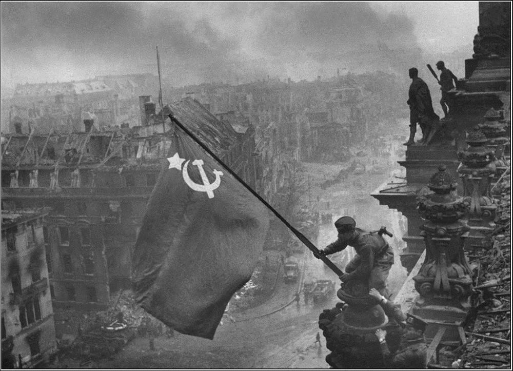 Soldados hasteiam a bandeira soviética sobre o Reichstag: esta é a célebre fotografia de Yevgeny Khaldei, tirada em 2 de maio de 1945. A foto mostra soldados soviéticos que levantam a bandeira da União Soviética sobre o prédio do Reichstag alemão após a Batalha de Berlim.