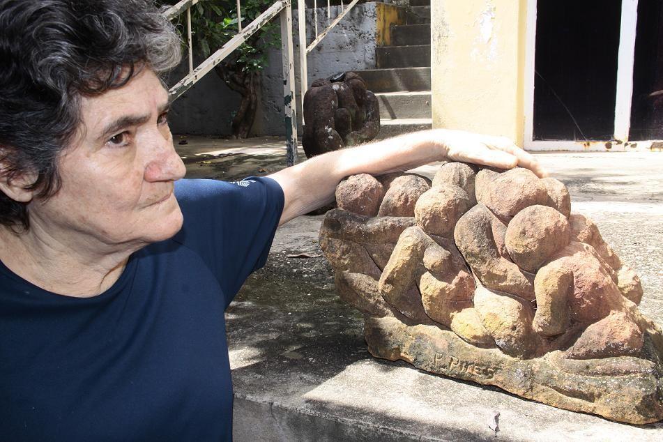 Aline Figueiredo posa ao lado da escultura em pedra de arenito de Paulo Pires,  do seu acervo particular. Foto Dinalte Miranda